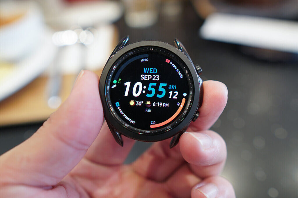 Samsung Galaxy Watch 3 held in a hand with the time and other complications.