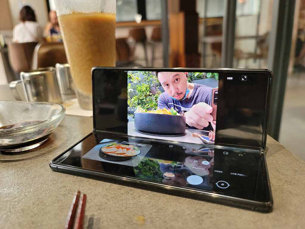 Samsung Galaxy Z Fold 2 folded up at right angle on a table, with flex mode on the camera app to take pictures