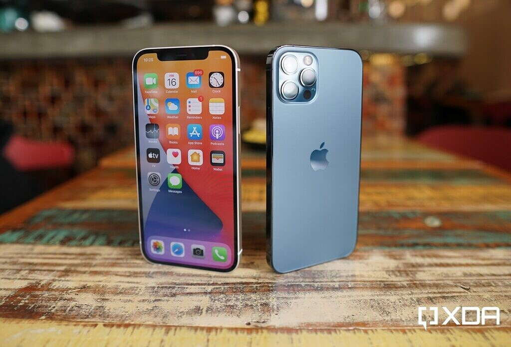 An iPhone 12 in white and an iPhone 12 Pro in blue on a table.