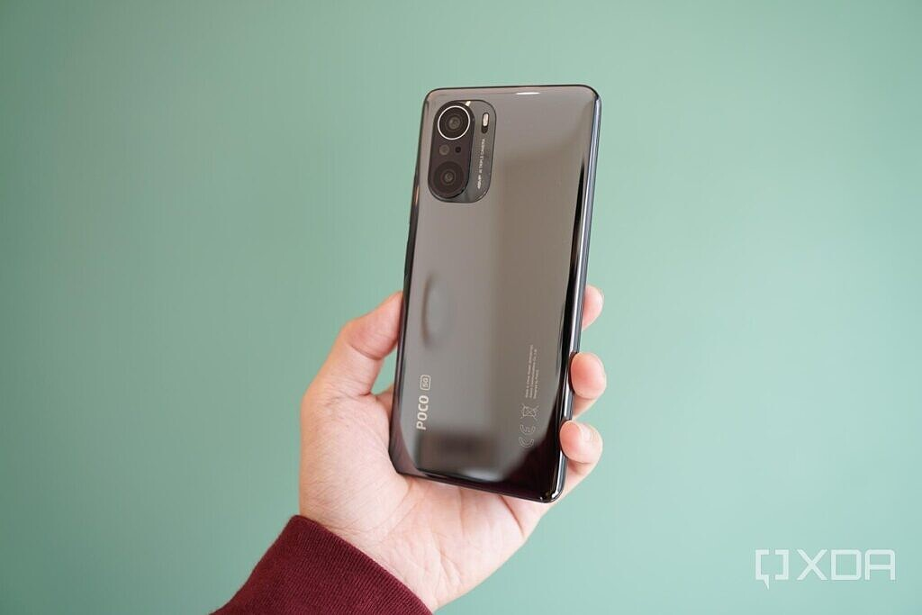 POCO F3 in silver held out in the hand