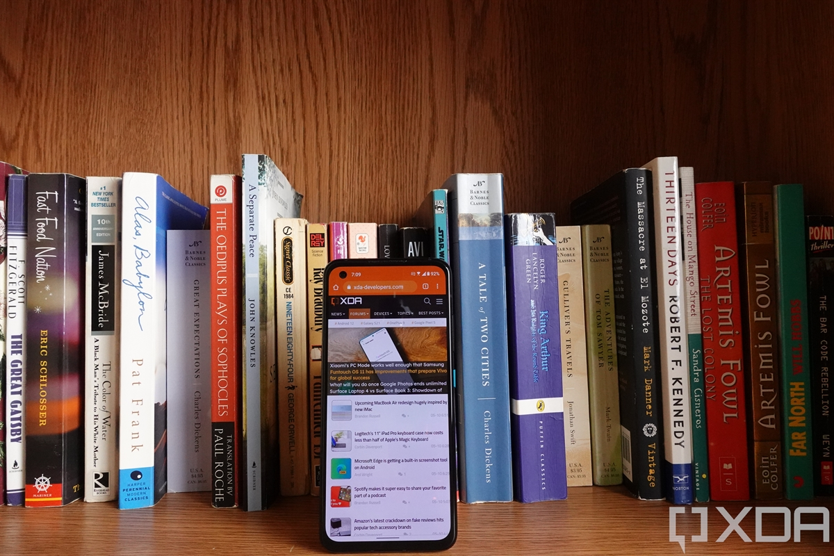 ASUS ZenFone 8 facing forwards in front of books on a bookshelf