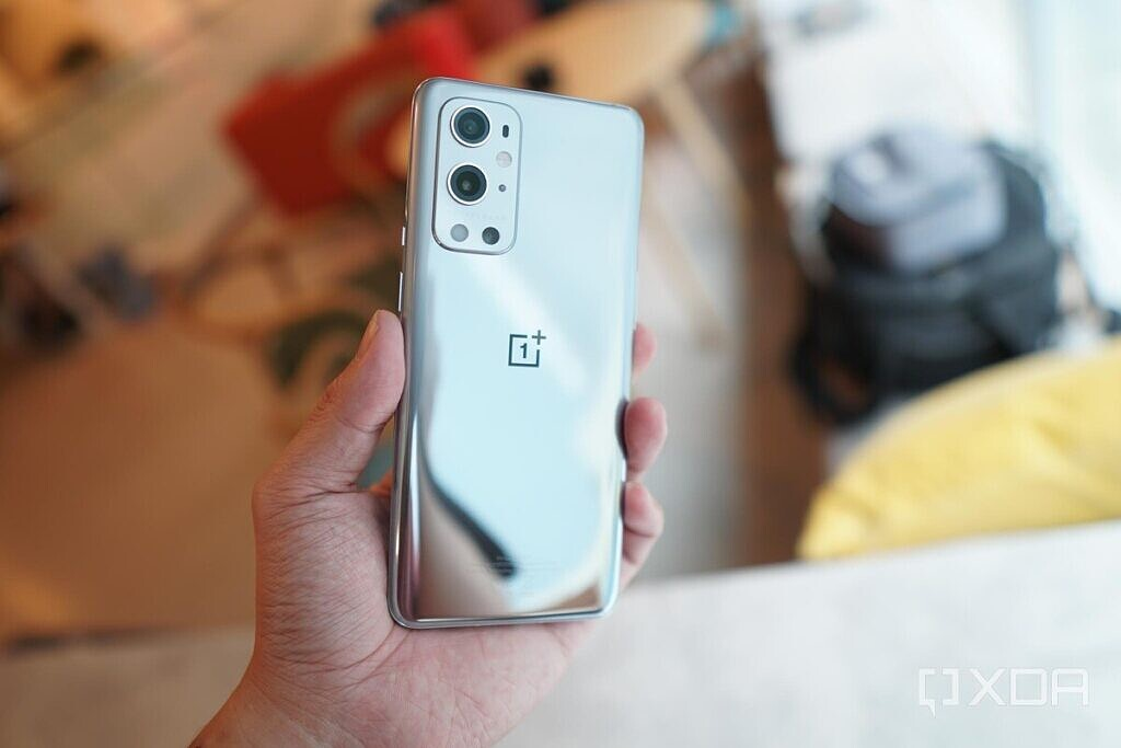 A silver OnePlus 9 Pro being held in the hand.