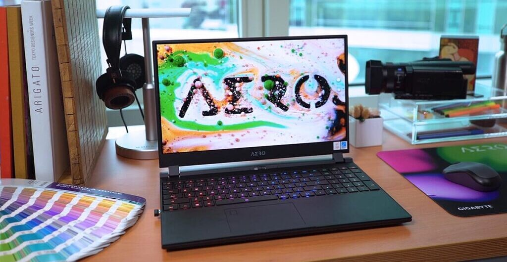 Gigabyte Aero 15 on desk with books and other items around