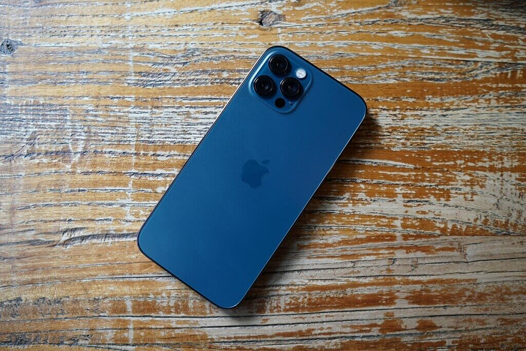 A blue iPhone 12 Pro on a table.