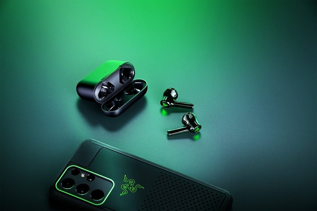 Hammerhead True Wireless X earbuds lying on their side alongside the charging case and a smartphone