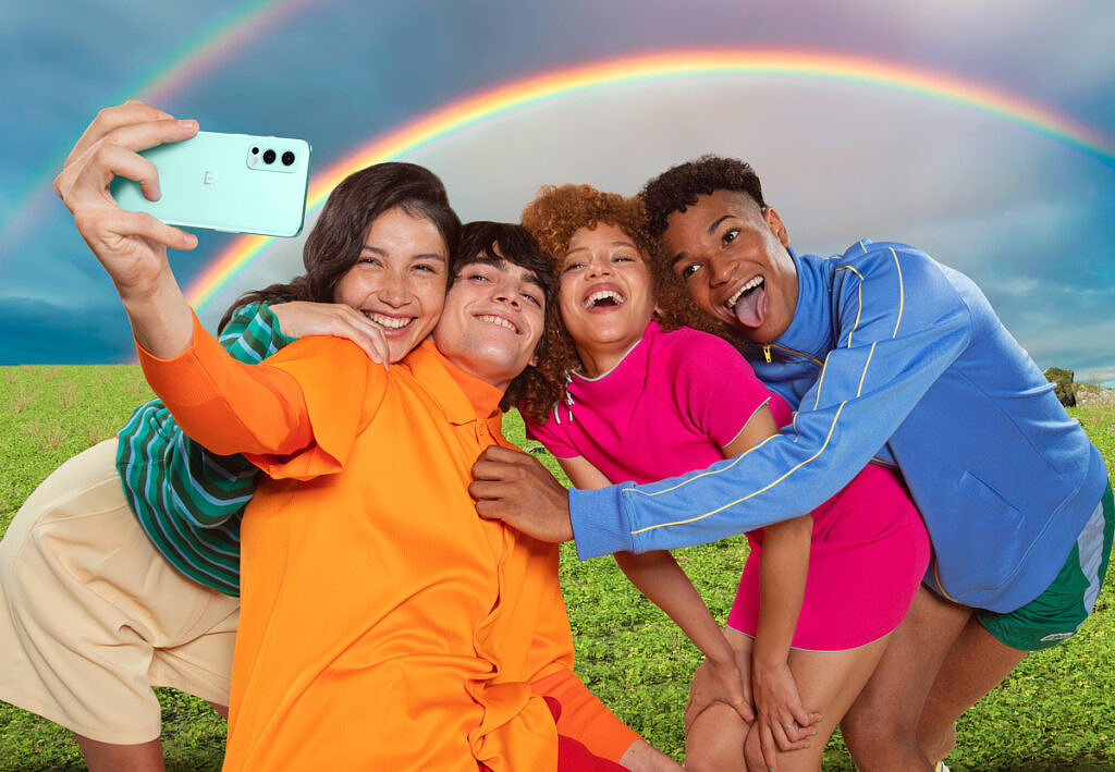 People posing with a rainbow in the background and clicking selfie photos with the OnePlus Nord 2 in hand
