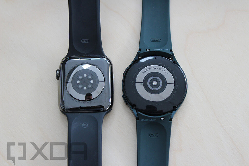 Bottom of Apple Watch and Samsung Galaxy Watch 4 with wooden background