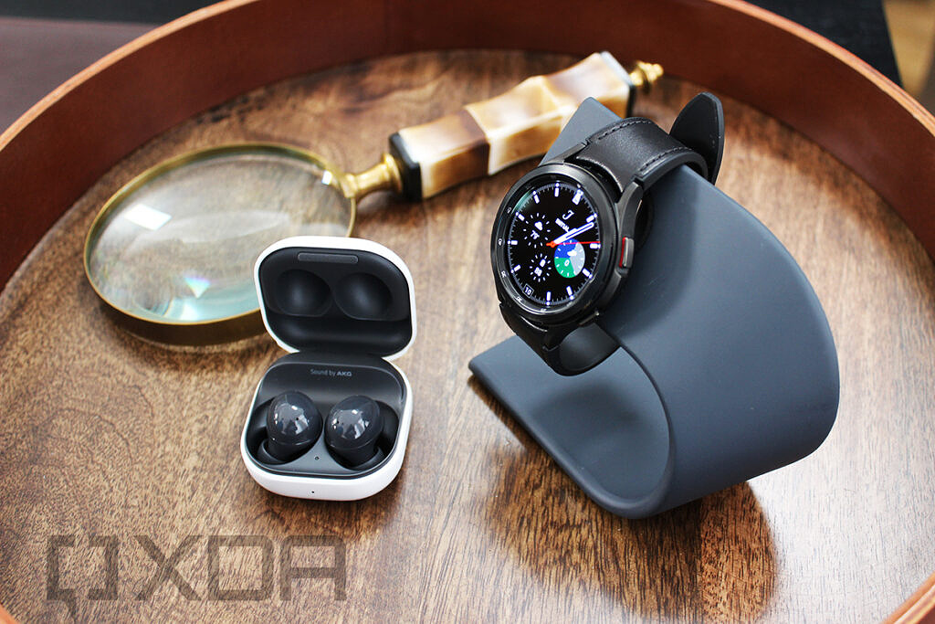 Samsung Galaxy Buds 2 and Galaxy Watch 4 with magnifying glass in background