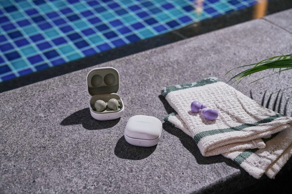 Samsung Galaxy Buds 2 in Olive Green and Lavender Purple kept besides a pool