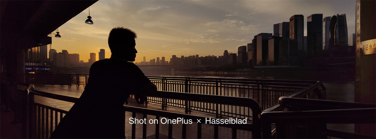 A photo shot with OnePlus9's XPan Mode depicting a person gazing at river with an open sky and buildings shown in the backdrop