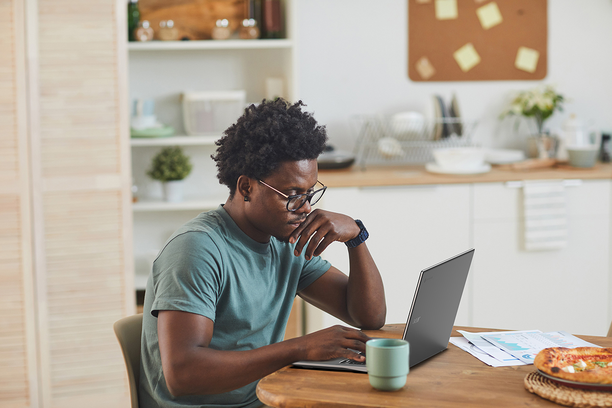 Man working on laptop with green cup