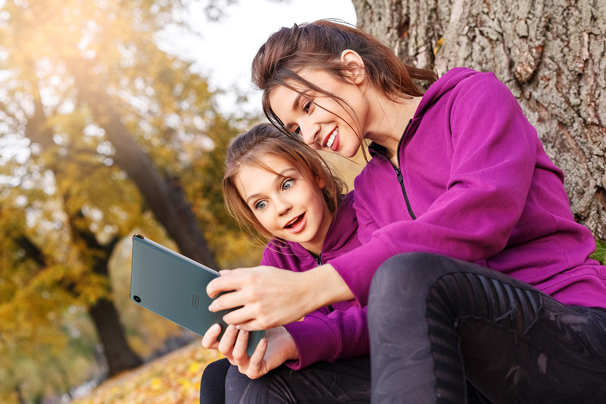 Woman and girl using tablet while sitting against a tree