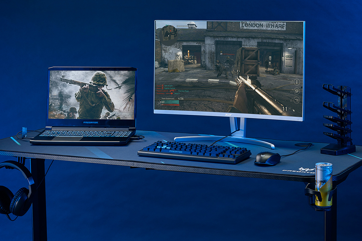 Desk with a laptop, keyboard, mouse, energy drink, and headset