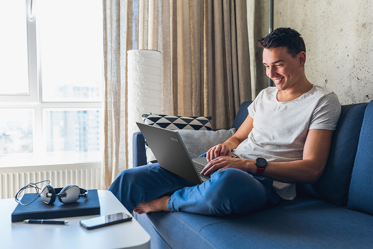 Man using laptop on a couch