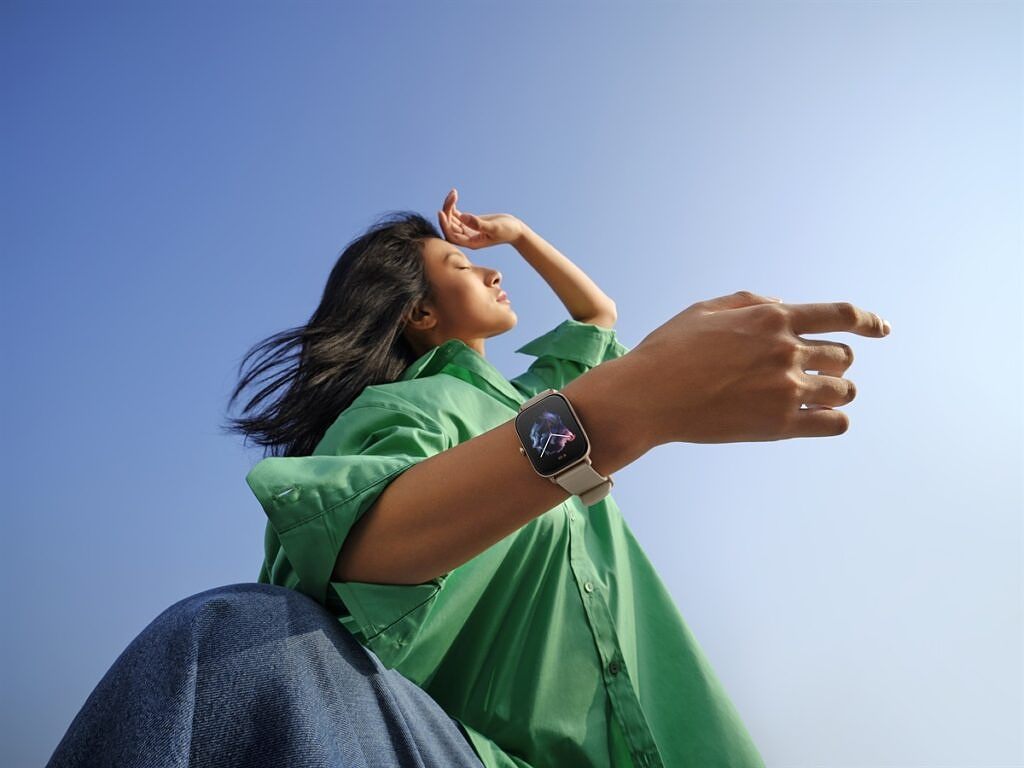 Amazfit GTS 3 on wrist with girl wearing green shirt