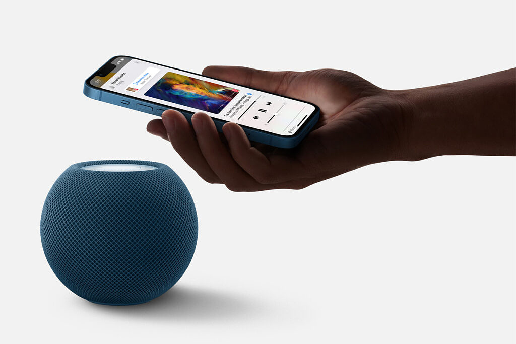 Apple HomePod Mini in blue with an iPhone next to it