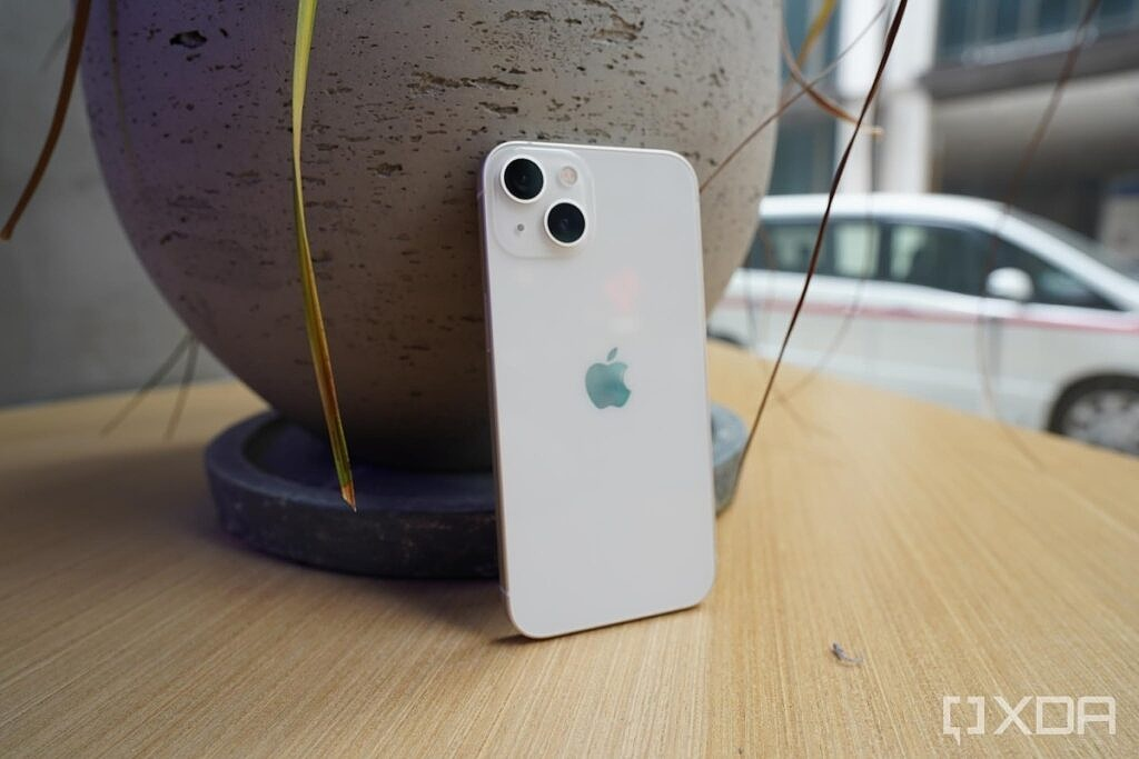 iPhone 13 Pro in white standing up against a vase