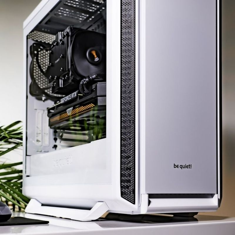 A white colored PC case resting on a table with some plants next to it