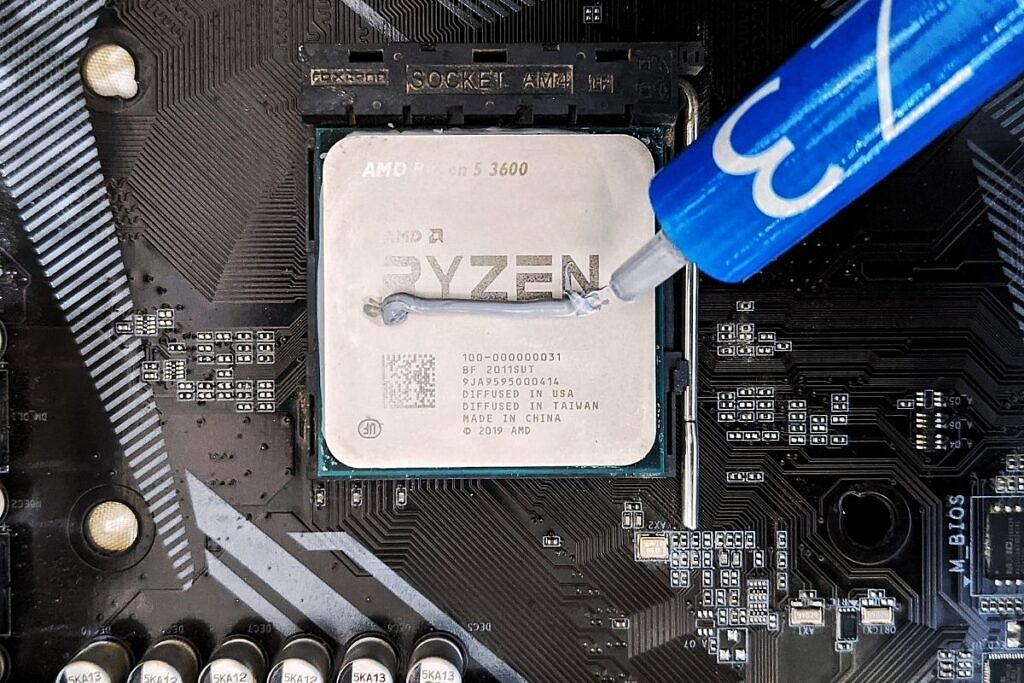 a line of thermal paste applied on an AMD Ryzen 5 3600 CPU